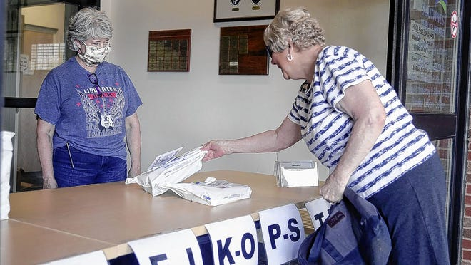 Jaymi Stout, with tech services, oversees pickups May 28 at the Grove City Library while Bonnie Swanson of Grove City retrieves her order as part of Southwest Public Libraries' curbside distribution program of items already held at Grove City and Westland Area libraries.