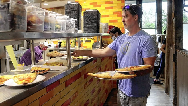 Mellow Mushroom regional manager Craig Brown brings out orders to customers June 25 at the restaurant in New Albany. The pizza shop will be one of the restaurants participating in Taste of New Albany on Aug. 2.