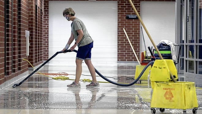 Custodian Barb Corbett vacuums excess water off the recently mopped floors July 16 at Central Crossing High School as the school prepares for reopening in Grove City.