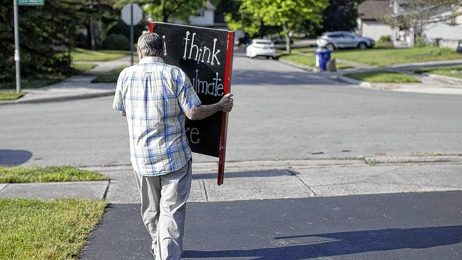 Karin Yoder's husband, Mike, carries the sandwich board with her daily inspiration to be displayed on the edge of the lawn near Loch Ness Avenue and Linworth Road.