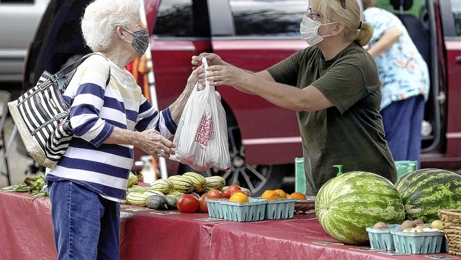 Nancy Dixon (left) of Reynoldsburg purchases produce from Chris Fields of Pheasantview Farms on Sept. 3 during the final Reynoldsburg Farmers Market of the summer season.