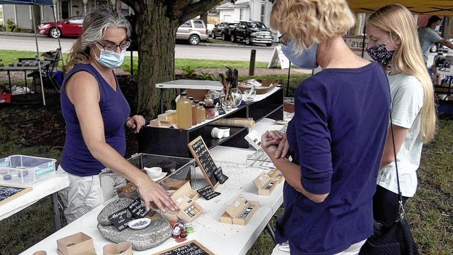 Christine Gruendemann (left), owner of Crafty Scribe, discusses her handmade art supplies for sale with Susan Grover of Canal Winchester and her granddaughter, Lilanna Stultz, 13, at the Canal Winchester Farmers Market on Aug. 29. Officials said an average of 450 patrons have visited each Saturday since the market opened May 30.