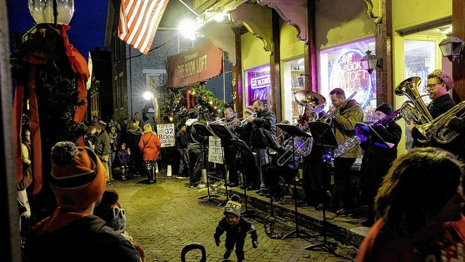 A brass band plays Christmas songs in front of the German Village Book Loft during the 2019 Village Lights event in German Village. This year, the event has been recast with a different format.