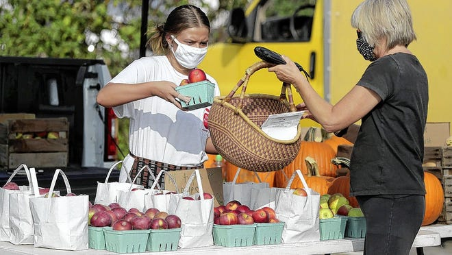 Kris Edwards (right) of Upper Arlington holds out a basket for Rachel Kelly from Paige's Produce to fill with apples Sept. 16 at the Upper Arlington Farmers Market. Although protocols are in place because of the COVID-19 coronavirus pandemic, the average market-day attendance increased from 350 last year to 450 this season. The final market is Wednesday, Sept. 30.