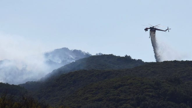 In this photo provided by the Santa Barbara County Fire Department, a Skycrane makes a water drop on hot spots near Hot Spring Canyon and Highway 154 in the Whittier Fire area near Santa Barbara on Wednesday.