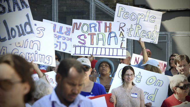 People hold signs during a rally and march to support the extension of the Northstar line to St. Cloud.