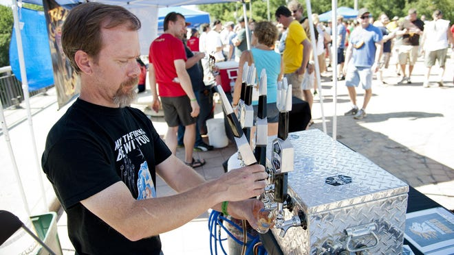 Jon W. Lang, master brewer and founder of Triton Brewing Company in Indianapolis, pours a sample as revelers line up at booths in the background during Beers Across the Wabash. This year's event is Saturday.