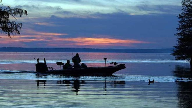 An angler motors across Toledo Bend at sunset. The reservoir has been chosen the country's top bass fishing lake for a second straight year.
