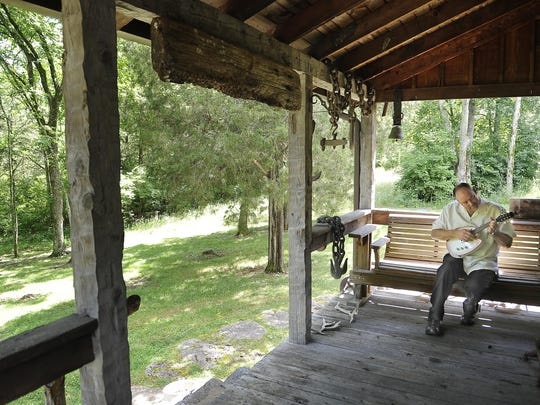 """John Carter Cash plays music on the porch of a small cabin that was converted into a recording studio on the family's land in Hendersonville. It was a """"getaway"""" spot for his father, Johnny Cash."""