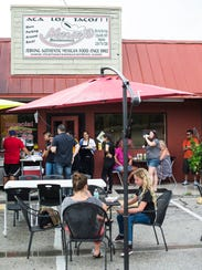 People line up after a downpour of rain for tacos outside