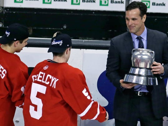 FILE - In this Feb. 23, 2015, file photo Boston University hockey head coach David Quinn, right, hands the Beanpot trophy to Matt Grzelcyk (5) and Evan Rodrigues, left, after their overtime win against Northeastern in Boston. NHL teams are thinking outside the box to find coaches. Quinn has been linked to the Rangers but will stay at least one more year and run the U.S. world junior team like Housley before likely being the next to graduate from college to the NHL. (AP Photo/Charles Krupa, file)