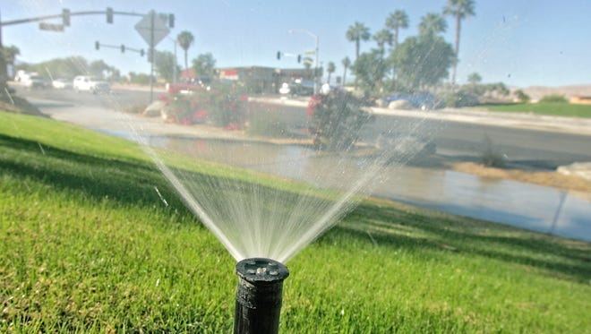 A sprinkler at a business on Dinah Shore Drive waters grass and some of the sidewalk.