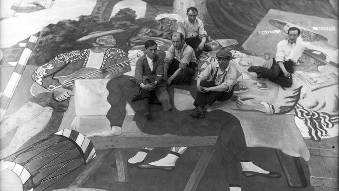 This glass negative by Lachmann shows the set of 'Parade' by Diaghilev Ballets Russes, in 1917, with Picasso (in cap) and scene painters.