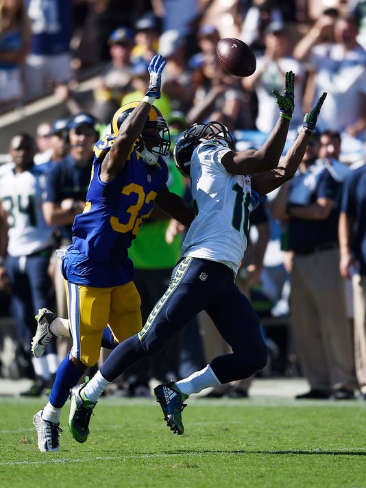 Seattle Seahawks wide receiver Tyler Lockett, right, makes a catch while under pressure from Los Angeles Rams cornerback Troy Hill during the second half of an NFL football game at the Los Angeles Memorial Coliseum, Sunday, Sept. 18, 2016, in Los Angeles. (AP Photo/Kelvin Kuo)