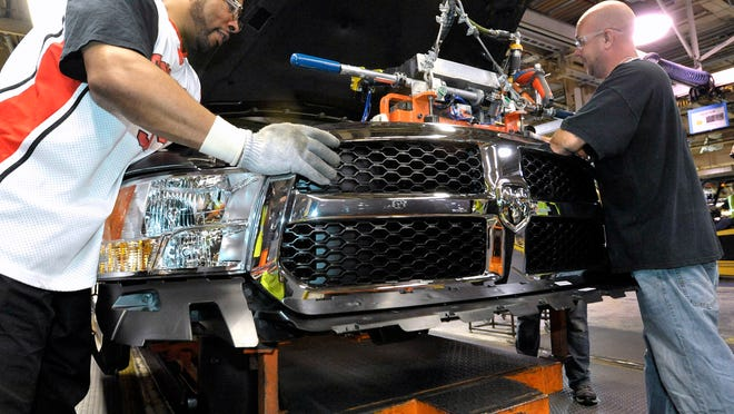 Stanford Martin, left, and Chris Ramsey install the front end module on a 2014 Ram 1500 at the Warren Truck Assembly plant.