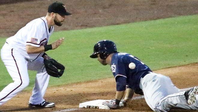 Michael Freeman of the Reno Aces slides into third base just ahead of the throw to El Paso Chihuahuas infielder Ryan Schimpf .