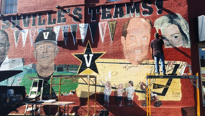 Artist Michael Cooper paints over the face of former Vanderbilt women's basketball coach Melanie Balcomb on the iconic mural on West End and 28th avenues.