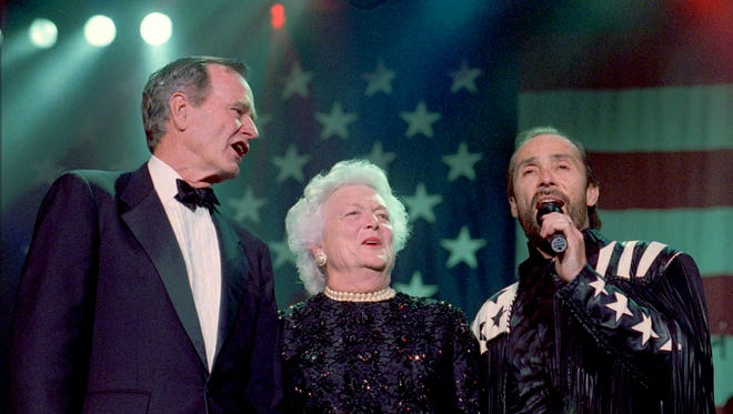 """Former President George H.W. Bush and wife Barbara assist singer Lee Greenwood in singing """"God Bless the USA"""" on April 1, 1996, in Sevierville, Tennessee, at the grand opening of the Lee Greenwood Theater. The song was made famous by Greenwood during the Gulf War."""