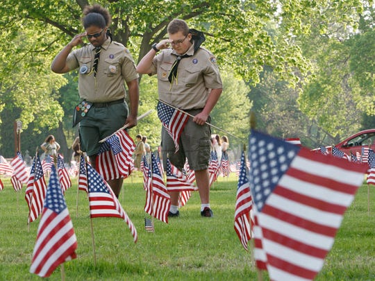 Cyone Marble, 14, left, and Sam Tschiderer, 14, both members of the Boy Scouts of America Troop 195 in Greece, salute after planting a row of flags at their Memorial Day Veterans' Ceremony and Reflagging at Holy Sepulchre Cemetery in Rochester Thursday, May 22, 2014.  The scout troup placed flags on over 5000 veterans graves.