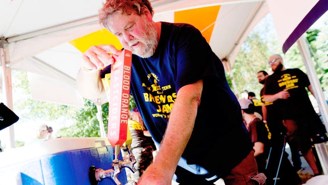 Jerry Satterfield, of Knoxville, pours beer samples for Austin Eastcider at the 21st annual Knoxville Brewers' Jam at World's Fair Park on Oct. 7, 2017. The event draws thousands of visitors from around the country and hosted 49 breweries in 2017.