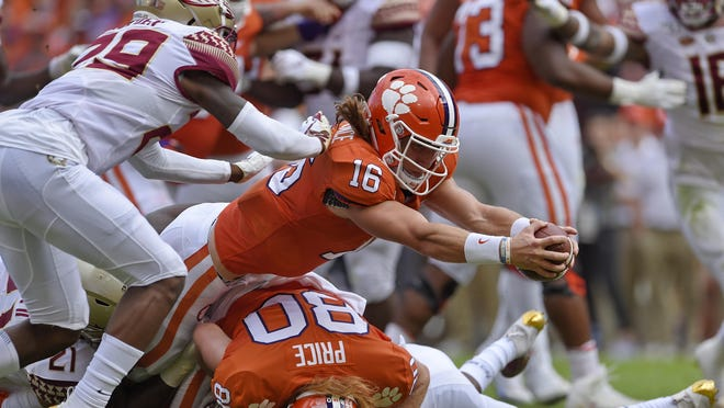 FILE - In this Oct. 12, 2019, file photo, Clemson quarterback Trevor Lawrence (16) stretches out for a touchdown while defended by Florida State's Isaiah Bolden (29) during the first half of an NCAA college football game in Clemson, S.C. Lawrence was selected to The Associated Press preseason All-America first-team, Tuesday, Aug. 25, 2020.