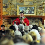Father Tommy Conway, founding priest at St. Fabian Catholic Church, closes Mass at the Lake Serene Clubhouse. More than 400 attended St. Fabian's first Mass in January.