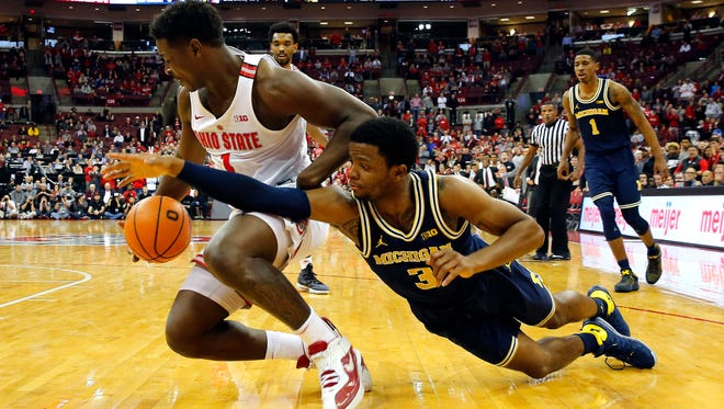Ohio State Buckeyes forward Jae'Sean Tate, left, steals the ball from Michigan Wolverines guard Zavier Simpson during the second half at Value City Arena in Columbus, Ohio.