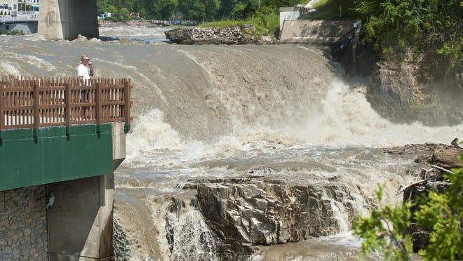 Water flows over the Winooski One Hydroelectric Dam in Winooski .