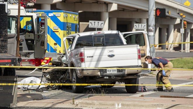 An Austin firefighter works at the scene of a fatal crash in the intersection of Todd Lane and the East Ben White Boulevard service road on April 20. At least 80 people have died so far this year in Austin traffic.