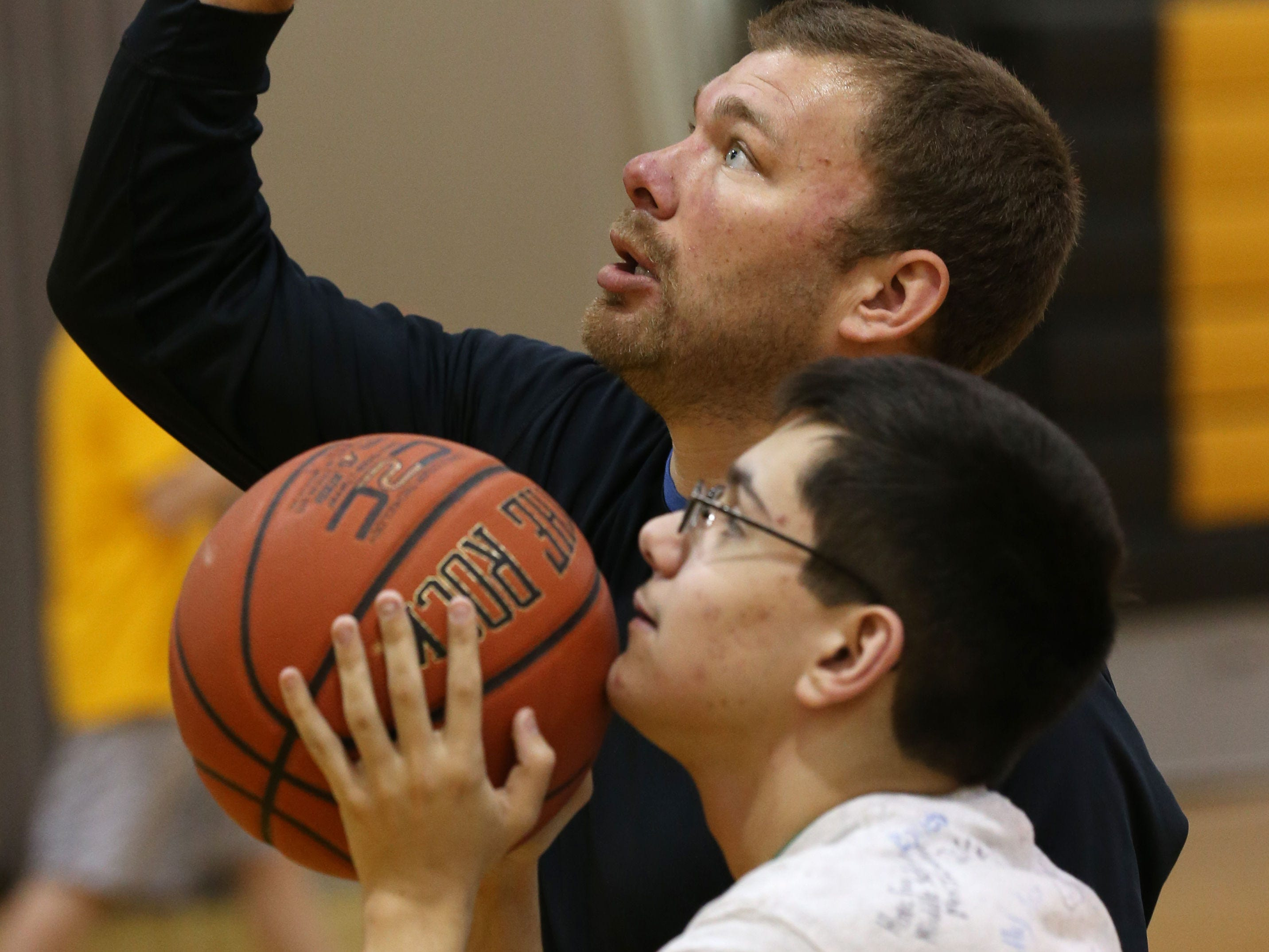 Peter Stakos gets a pointer from Asstistant Coach Cory Quinter, during the second practice for Honeoye Falls-Lima's unified basketball team.