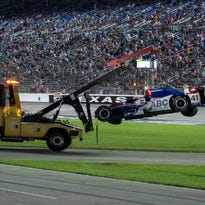 The car of  AJ Foyt Enterprises driver Jack Hawksworth (41) of England is hauled off after wrecking during the Firestone 600 at Texas Motor Speedway.