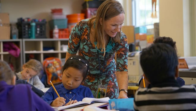 Mount Pleasant Elementary second-grader Erin Kang, 8, works on a class assignment as teacher Wendy Turner stands behind her. Turner was named Delaware's 2016 Teacher of the Year.