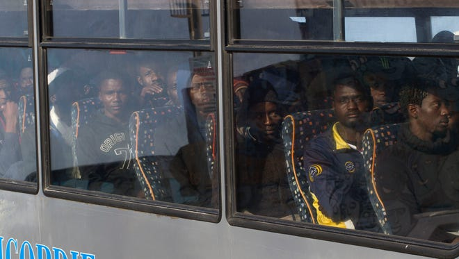 Rescued migrants sit on a bus after disembarking from an Italian Coast Guard ship in the harbor of Lampedusa, Southern Italy. Ships from Italy and France rescued almost 3,700 migrants on Saturday after smugglers' boats ran into trouble in the Mediterranean Sea near Libya.