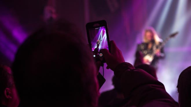 A fan films a Judas Priest performance at the Riverside Theater on April 3. More performers like Bob Dylan and Kevin Hart are insisting on phone-free concerts, with some artists, including Jack White and Chris Rock, requiring showgoers to lock their phones in portable pouches provided by San Francisco-based Yondr.