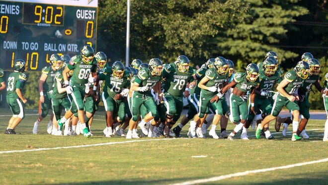 Christ School's football team takes the field during a game last year.