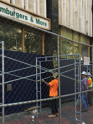 Workers put up fencing after the Shelby County Environmental Court ordered improved security at the vacant 100 North Main skyscraper. T