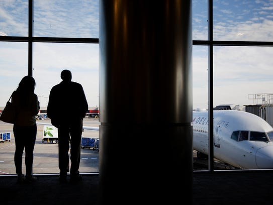 Travelers look out a window while waiting to board