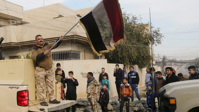 An Iraqi soldier waves the national flag as security forces patrol on the eastern side of Mosul, Iraq, on Jan. 18, 2017.