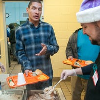 Volunteer Marli Tellez fetches a tray of green chile from the back refrigerators at El Caldito Soup Kitchen on Thursday during the annual Thanksgiving dinner.