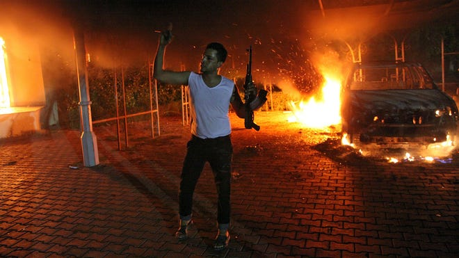 An armed man waves his rifle as buildings and cars are engulfed in flames after being set on fire inside the U.S. consulate compound in Benghazi on Sept. 11, 2012.