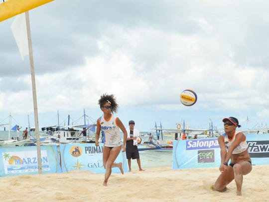 Tatiana Sablan, right, receives serve while teammate