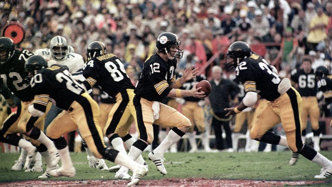 Pittsburgh Steelers quarterback Terry Bradshaw hands off to running back Franco Harris during Super Bowl XIII against the Dallas Cowboys on Jan. 21, 1979.  The Steelers won 35-31 as Bradshaw threw four touchdown passes and was named MVP.