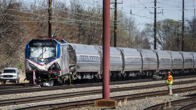 An Amtrak train sits on the tracks after it struck a piece of construction equipment on the tracks in Chester, Pa. on Sunday morning.