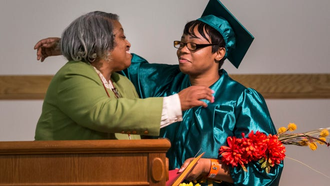 Ashley Richardson (right) hugs Program Coordinator Paula Stevens during ceremonies for women graduating from the Delaware Mentor Program at the Baylor Women's Correctional Institution in New Castle on Tuesday evening.