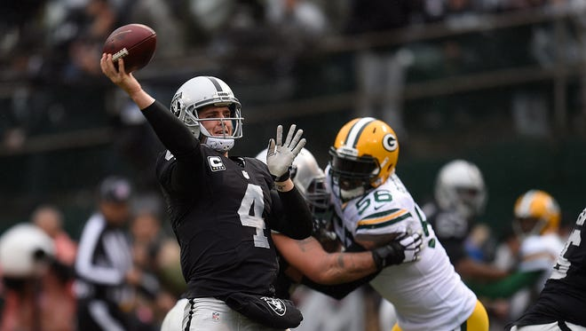 Oakland Raiders quarterback Derek Carr (4) makes a pass while being pressured by Green Bay Packers linebacker Julius Peppers at O.co Coliseum.