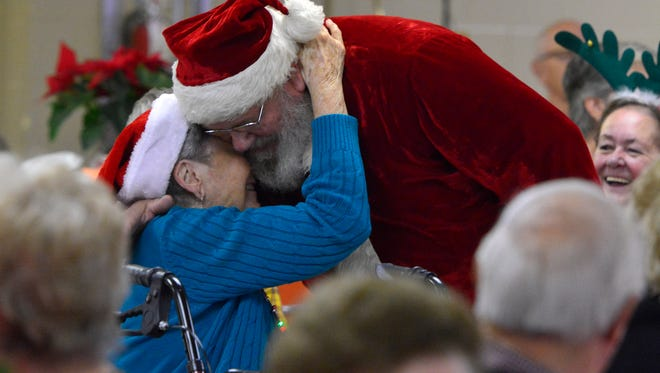 Kay Arians, 90 of Hanover, gets a hug from Santa during the Windy Hill Senior Center Christmas celebration, Thursday Dec. 17, 2015.  (John A. Pavoncello - The York Dispatch)