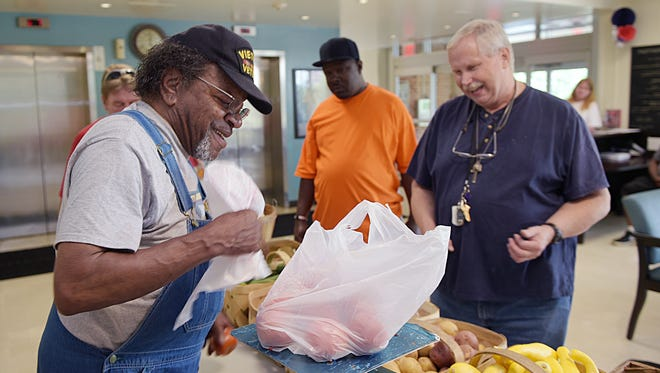 Farmer Bobby Gooch sells his fresh produce at Parthenon Towers on Saturday, July 2, 2016. Gooch sells tomatoes to resident Jim Gordon in the lobby.