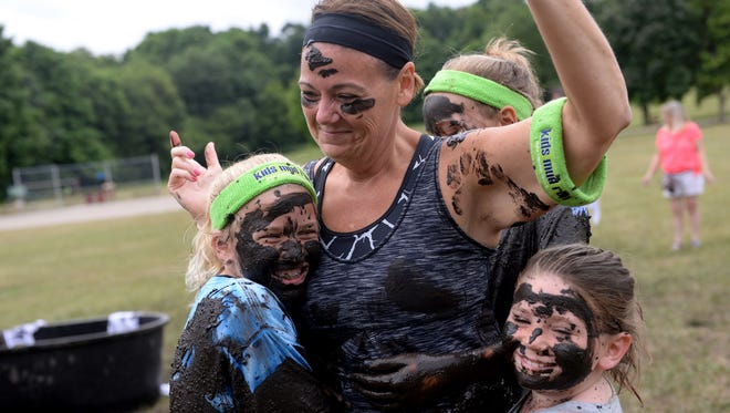 Amy McNamara tries to avoid getting mud on her as Coralie Allison, 11, left, Bri Spalding, 11, behind her, and her daughter Lexi McNamara, 7, give her a hug at Kids Mud Run on Saturday, July 16, 2016 at Grand Woods Park in Lansing.