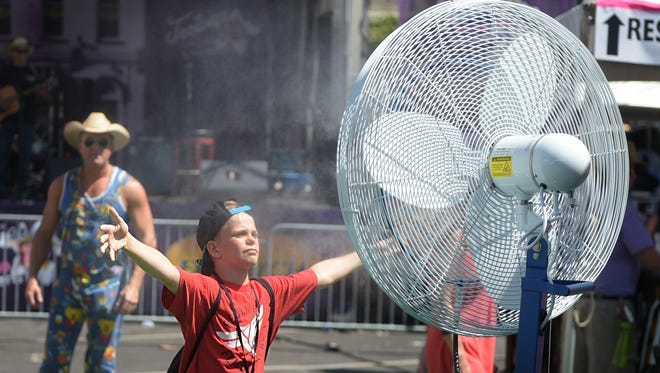 Ryder Powell,10, uses a misting fan to cool down during CMA Music Festival on Friday, June 10, 2016.