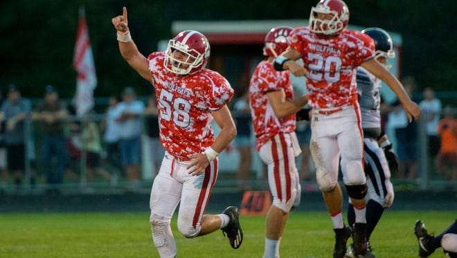 Laingsburg's Holden Patterson celebrates a Wolfpack fumble recovery during the first half of Laingsburg's game against the Eagles on Friday, Sept. 22, 2017, at Laingsburg High School.